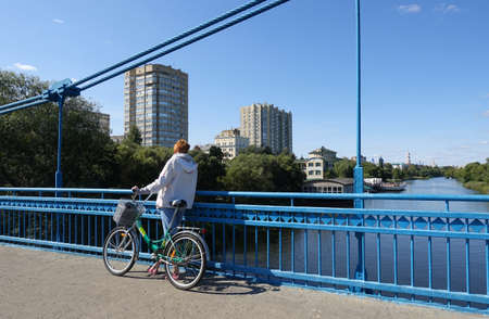 A woman with a bicycle standing on the bridge admires the view of the Tsna and Tambov river on a summer day