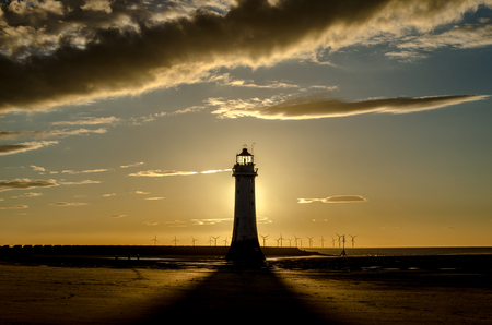 mersey: Silhouette of backlit lighthouse in sunset Stock Photo