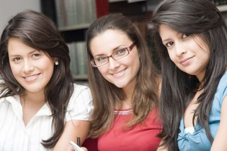Portrait of three students studying in a library Stock Photo - 6329363