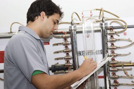 cilindro de gas: Hombre trabajando con v�lvulas y tuber�as en una planta