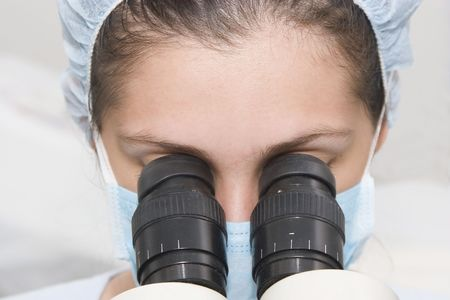Medical  professional looking through a microscope photo