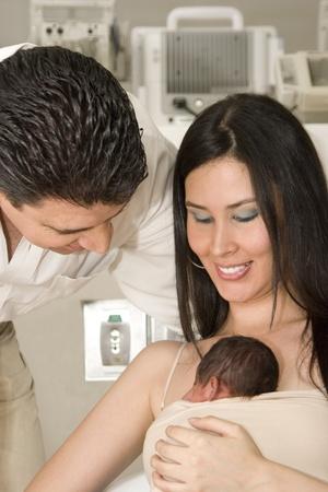 papa y mama: Retrato de familia, mam�, pap� y beb� reci�n nacido disfrutando juntos de interior Foto de archivo