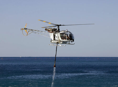 FIRE FIGHT HELICOPTER WITH WATER BUCKET AT SEA Archivio Fotografico