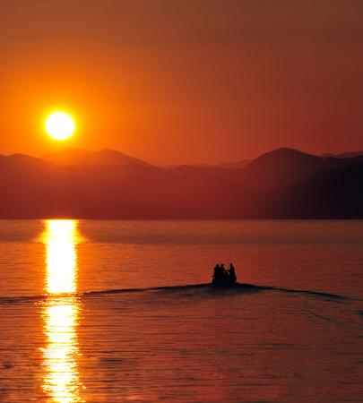 fishermen boat leaving harbour at sunset