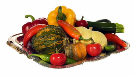 silver plate filled with peppers, pumpkins and courgettes isolated on white background