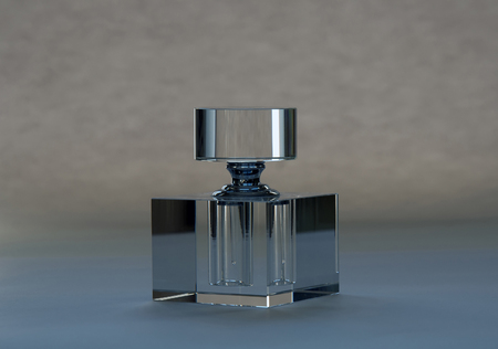 A crystal bottle for perfume essence on bluish grey background