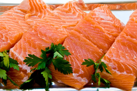 Four chunks of salmon fillet on a silver dish with parsley leaves Archivio Fotografico