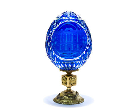 Blue cobalt carved crystal egg on bronze stand with eagles Archivio Fotografico