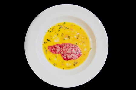 A piece of beef brain in a white dish with beaten egg and parsley ready to be fried.