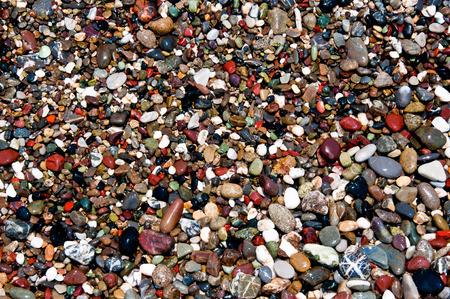 multicolor stone pebbles washed by sea water on an italian beach near Portofino