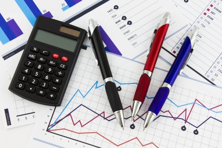 pens and calculator on financial chart photo