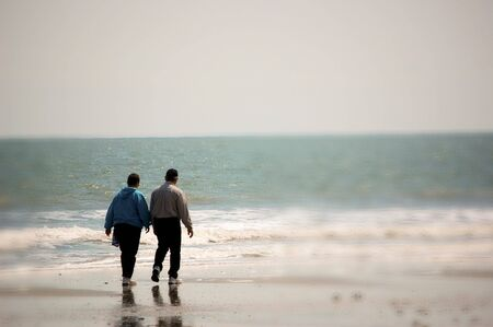 Older Couple Walking On The Beach photo