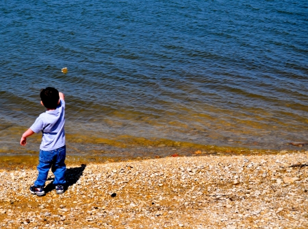 tosses: Little boy tosses the rock
