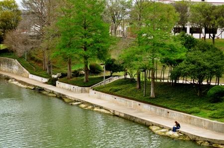 Waco woman reads on bank of river Standard-Bild