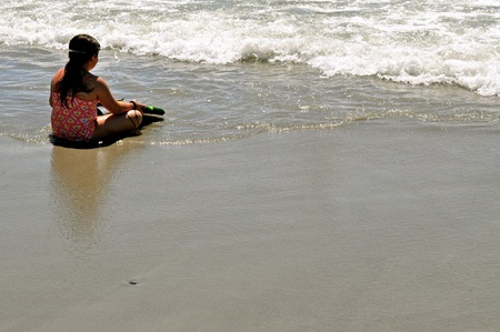 Little Girl waits to surf in the ocean photo
