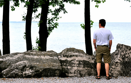 erie: Man Looks Out On Lake Erie Stock Photo