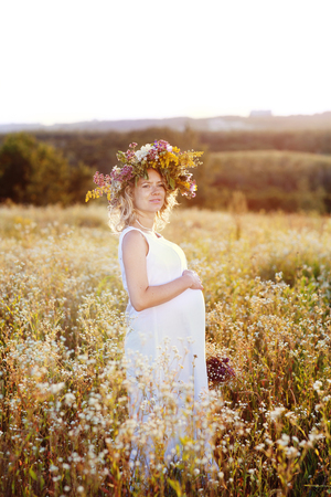 Beautiful and happy pregnant woman in a white dress on the nature in the summer, around the trees and flowers. Stock Photo