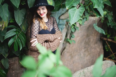 Young beautiful pregnant woman in hat and cardigan among tropical plants Stock Photo - 116708034