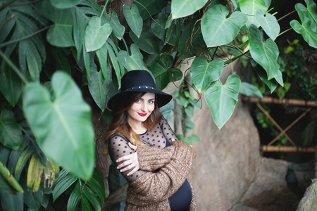 Young beautiful pregnant woman in hat and cardigan among tropical plants