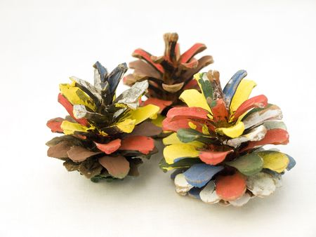 Three multi-colored pine cones, decorated paint on a white background.