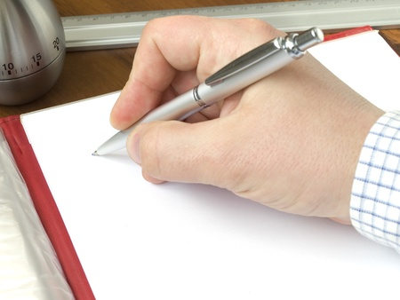 Hand holding a ball pen, timer, measuring ruler, sheet of a paper laying on a desk