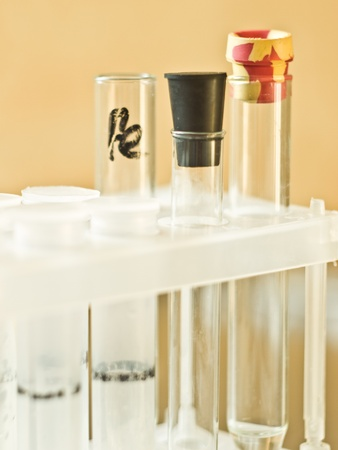 Glass and plastic vials in a plastic tripod stand on a yellow background