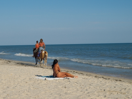 The woman on the shore, watching the two women, galloping on horseback photo