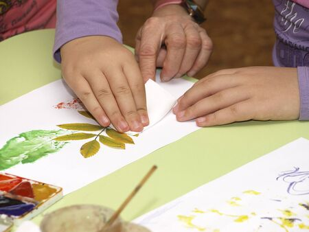 Hands of the child and grandmother draw