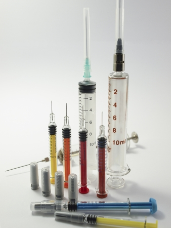 Syringes of different colors and sizes on grey background Stock Photo