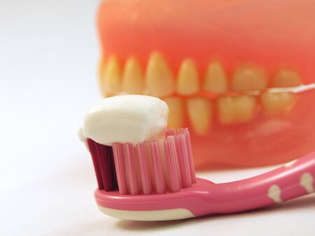 White toothpaste on the toothbrush on a background of yellow teeth