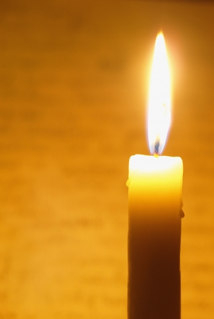 esoterik: Brightly flaring candle on a yellow background Stock Photo