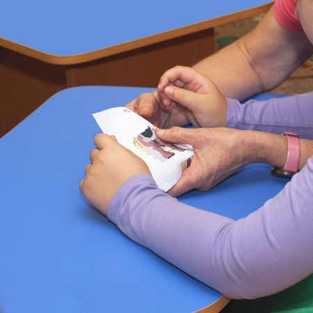 Hands of the girl embroider, preschool education Stock Photo