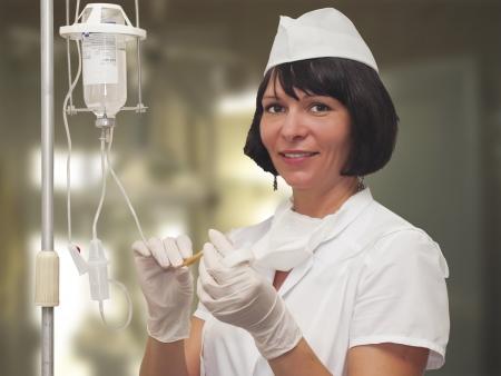 kesztyű: Gyönyörű fiatal nővér készül, hogy tartsa intravénás csepegtető gyógyszert