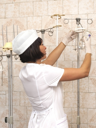 populate: Beautiful young nurse preparing to hold intravenous drip medication