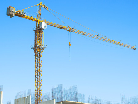 Crane against the blue sky above the concrete blocks photo