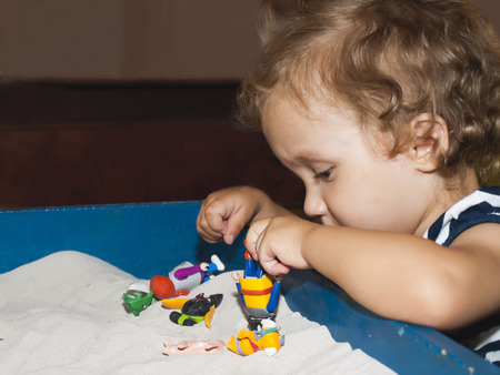 The little girl plays toys in sand, therapy