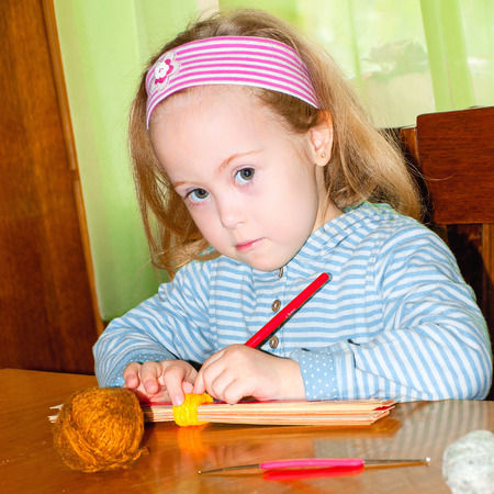 The child plays with crochet hooks, syndrome, down syndrome Stock Photo