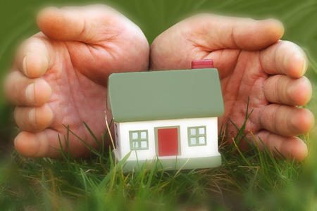 a persons palm concealing toy house in the grass Stock Photo