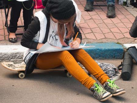 left handed: Teenage original artist draws a pencil sitting on a skateboard Stock Photo