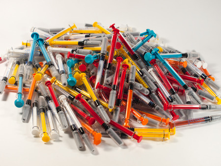 dependency: Syringes of different colors and sizes on grey background Stock Photo
