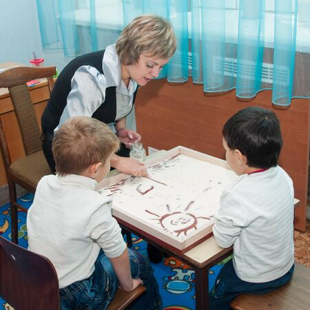 Girl-specialist gives classes of sand therapy with children