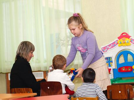 niños actuando: Los niños y la mujer que juega en el teatro, el niño comienza a jugar
