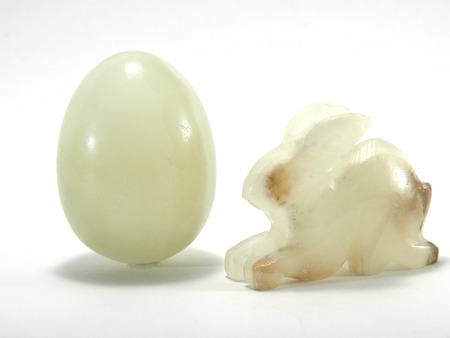 Egg and rabbit made of stone on a white background