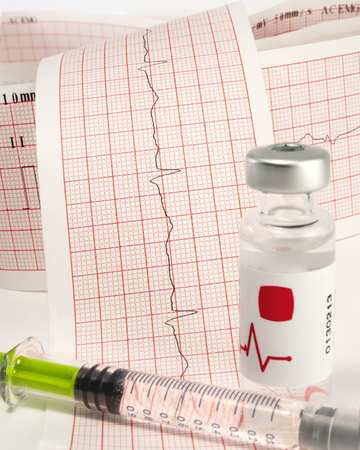 electrocardiograph: Syringe and vial on electrocardiograph.