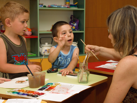 communicates: Woman communicates with children in art class