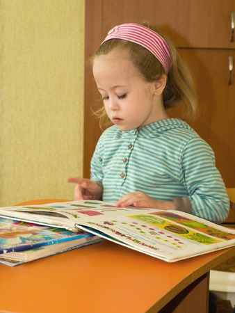 enthusiastically: Little girl enthusiastically reviews books on the table Stock Photo