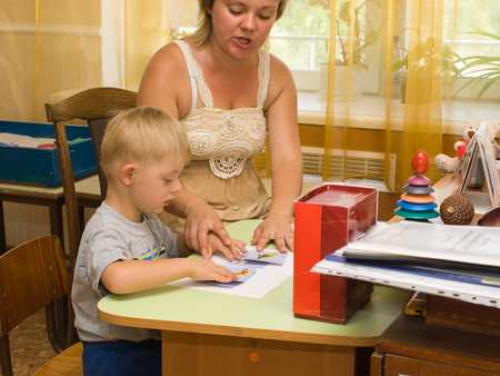 capable of learning: Psychologist and a child with Down syndrome perform a task in the classroom