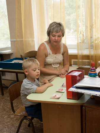 Down Syndrome: Psychologist and a child with Down syndrome perform a task in the classroom