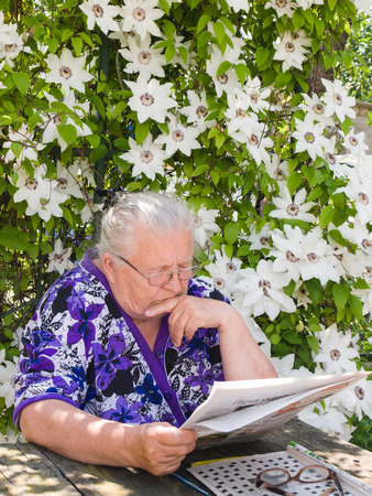 Grandmother reading a newspaper in the garden under a bush of flowers
