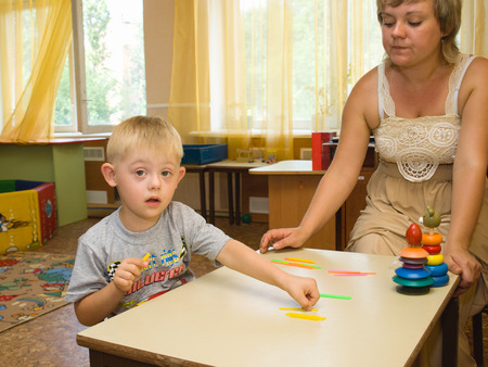 Psychologist and a child with Down syndrome perform a task in the classroom
